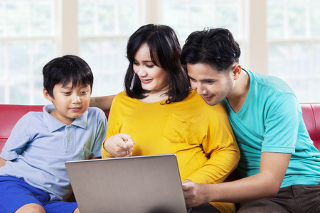 Portrait of father and mother teach her son with a laptop computer at home photo