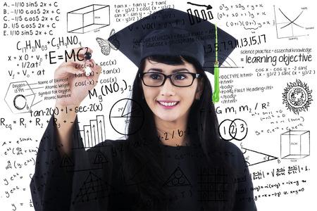glassboard: Female student writing math formulas on the transparent whiteboard Stock Photo