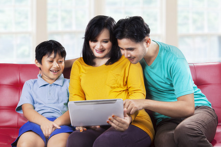 Happy asian family using digital tablet on couch, shot at home