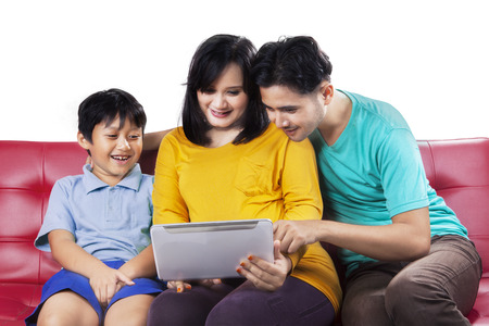 Portrait of happy asian family using digital tablet on couch, isolated over white background photo