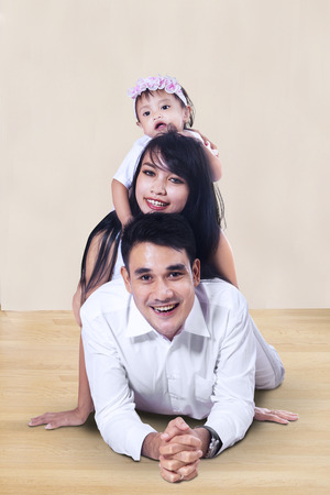 Portrait of happy family with baby girl lying on the floor photo