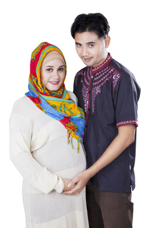 Happy islamic pregnant female and her husband in studio, isolated over white background photo
