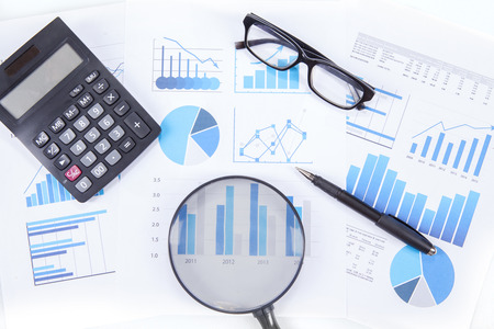 angle bar: High angle view of magnifying glass with business chart, calculator, glasses, and pen Stock Photo