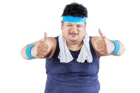 Portrait of fat man wearing sportswear with thumbs-up, isolated over white background photo