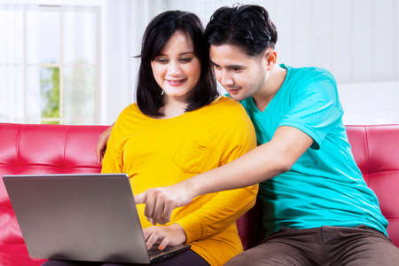Portrait of asian man with wife pregnant using laptop on couch photo