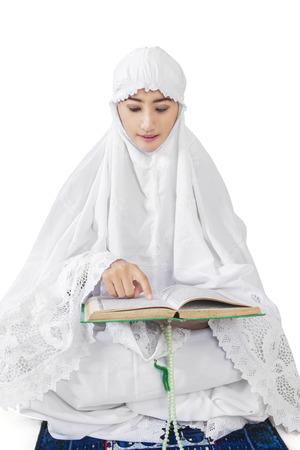 kuran: Bella donna musulmana leggere Kuran su sfondo bianco