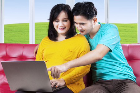 Attractive pregnant mother with her husband using laptop on sofa at home photo