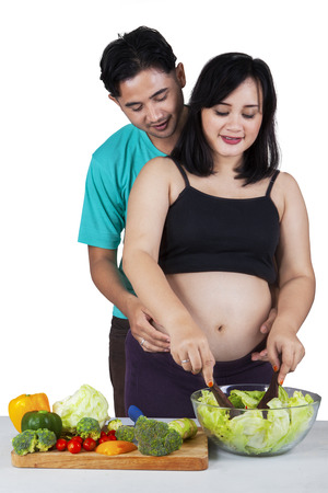 Pregnant woman and her husband prepare vegetable salad, isolated over white background photo