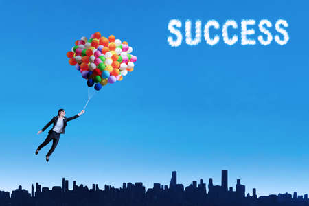 high spirits: Businesswoman flying with balloons over cityscape to get success Stock Photo