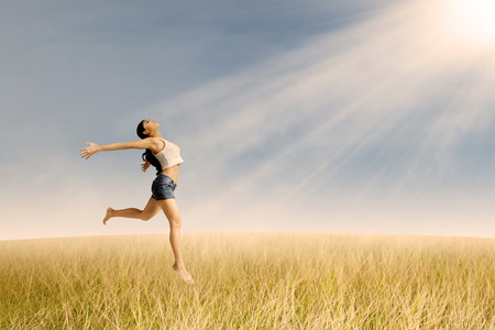 Portrait of a happy woman jumping in wheat field photo