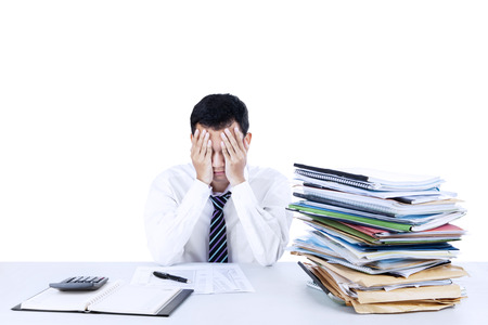 calculator chinese: Young businessman overwhelmed with stack of files on the desk Stock Photo