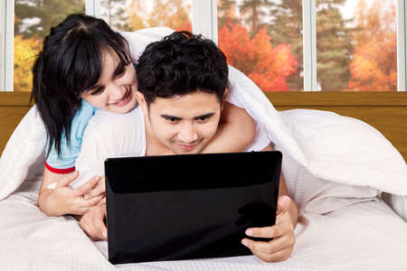 Young couple using laptop computer on bedroom at home in autumn photo