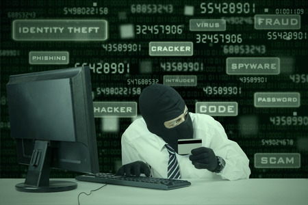 security monitor: Internet Theft - businessman wearing a mask and holding a credit card while sat behind a computer Stock Photo