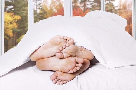 Feet of two couple sleeping on bed with autumn background on the window Stock Photo