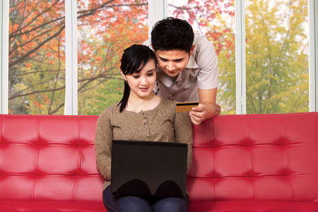 Asian couple using laptop computer and credit card to buy online at home in autumn photo
