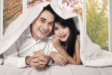 Young asian couple smiling at camera under blanket in bedroom with autumn background on the window photo