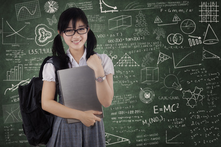Young asian female student holding laptop and smiling at camera in classroom
