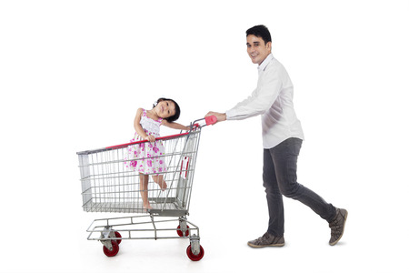 Young father pushing a shopping cart with his daughter inside it, isolated over white