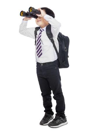 Little elementary school student using binoculars in studio, isolated over white photo