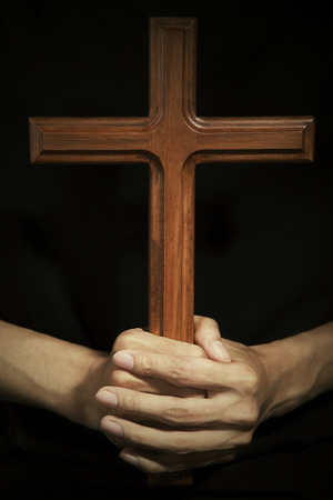 worshiper: Close-up of male hand holding wooden cross