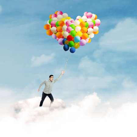 Young man flying in blue sky holding colorful balloons photo