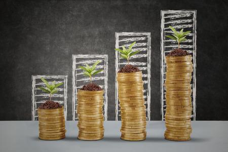 Planten groeien op de gouden geld munten met zakelijke grafiek achtergrond