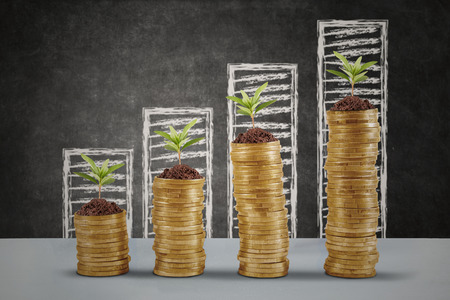 Plants growing up on the golden money coins with business graph background Stock Photo
