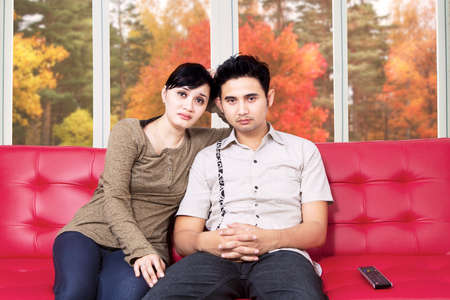 Asian couple watching tv and feel sad together at home in autumn photo