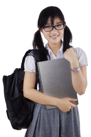 Portrait of cheerful female student holding laptop computer, isolated over white background