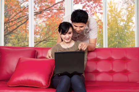 surfing the internet: Man pointing at laptop to choose something on laptop while his wife using the laptop