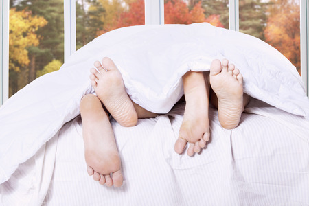Close up of couple feet on the bedroom with autumn background on the window photo