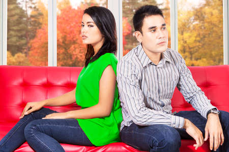 2 november: Asian couple sitting separately on sofa after quarreling at home Stock Photo