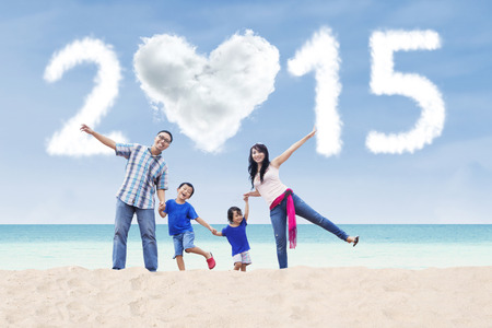 Cheerful asian family playing at beach under cloud of 2015 photo