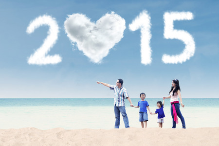 Young asian family holding hands and walking at beach under cloud of 2015 photo