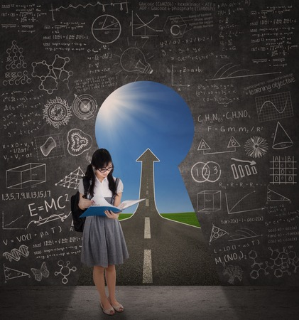 Full length of female student reading document in front of a key hole door photo