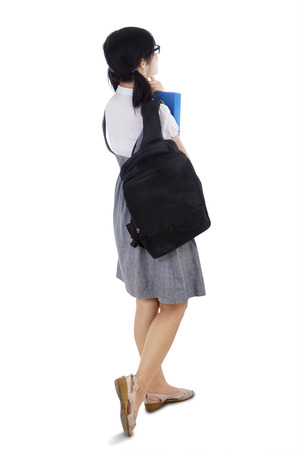 Rear view of female college student carrying backpack walking in studio, isolated over white