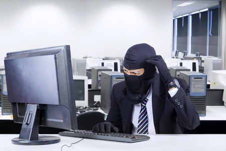 Male hacker wearing business suit getting confused to break the computer security photo