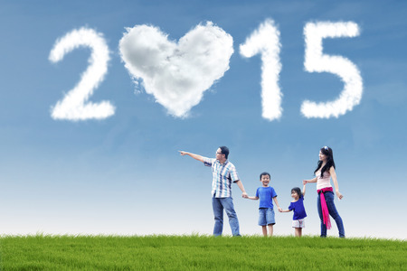 Attractive young asian family walking in field and holding hands under cloud of 2015 photo