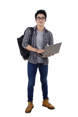 Full length of male student carrying backpack and holding laptop computer in studio, isolated over white background photo