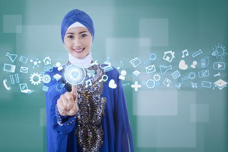 Young muslim businesswoman using modern business interface photo