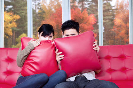 afraid man: Asian couple covering their face while watching horror movie at home in autumn