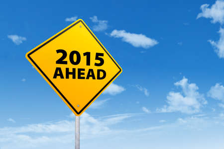 Yellow road sign with a text of 2015 ahead under blue sky photo