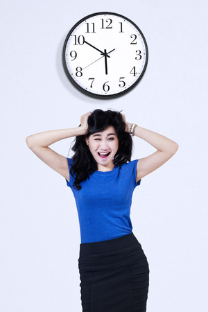 scratching head: Stressed business woman scratching her head under a wall clock Stock Photo