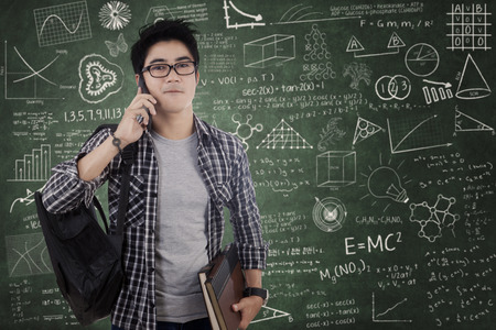 Male asian student carrying backpack and talking on cellphone in classroom photo
