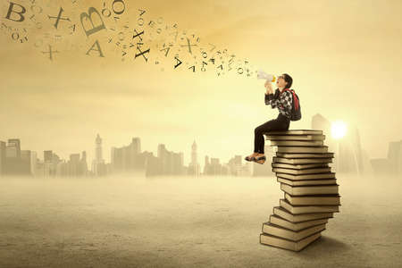Female student sitting on a stack of books and yelling with a megaphone Stock Photo