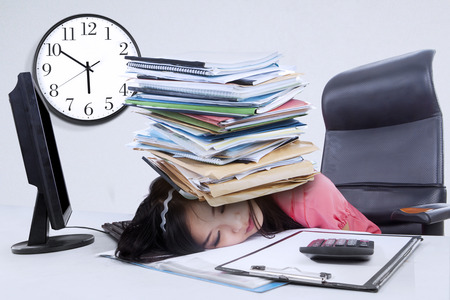 Overworked businesswoman sleeping in office with a pile of document on her head photo