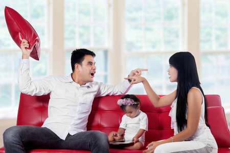 Young asian parents quarreling at home between their baby on sofa photo