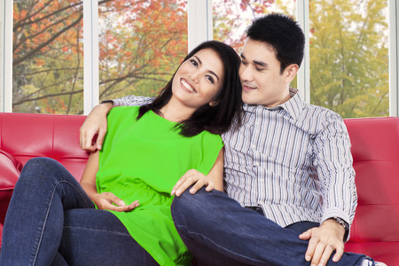 Attractive asian woman sitting on sofa with her boy and smiling at camera photo