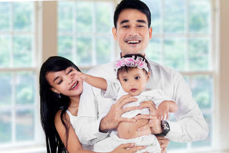Portrait of asian family smiling at camera, shot indoors in new home photo