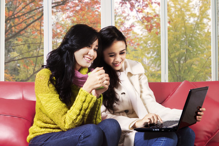 sitting pretty: Two young hispanic girl wearing a sweater and using laptop on sofa with autumn background on the window